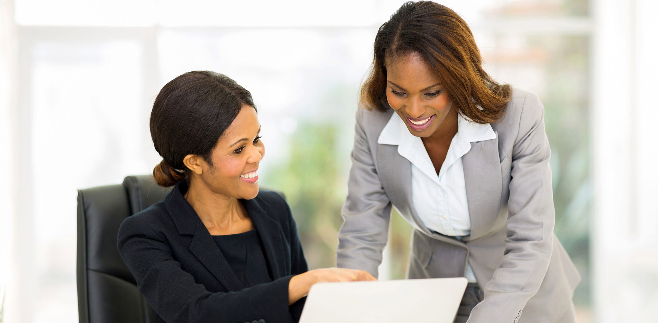 Two business women smiling and working together